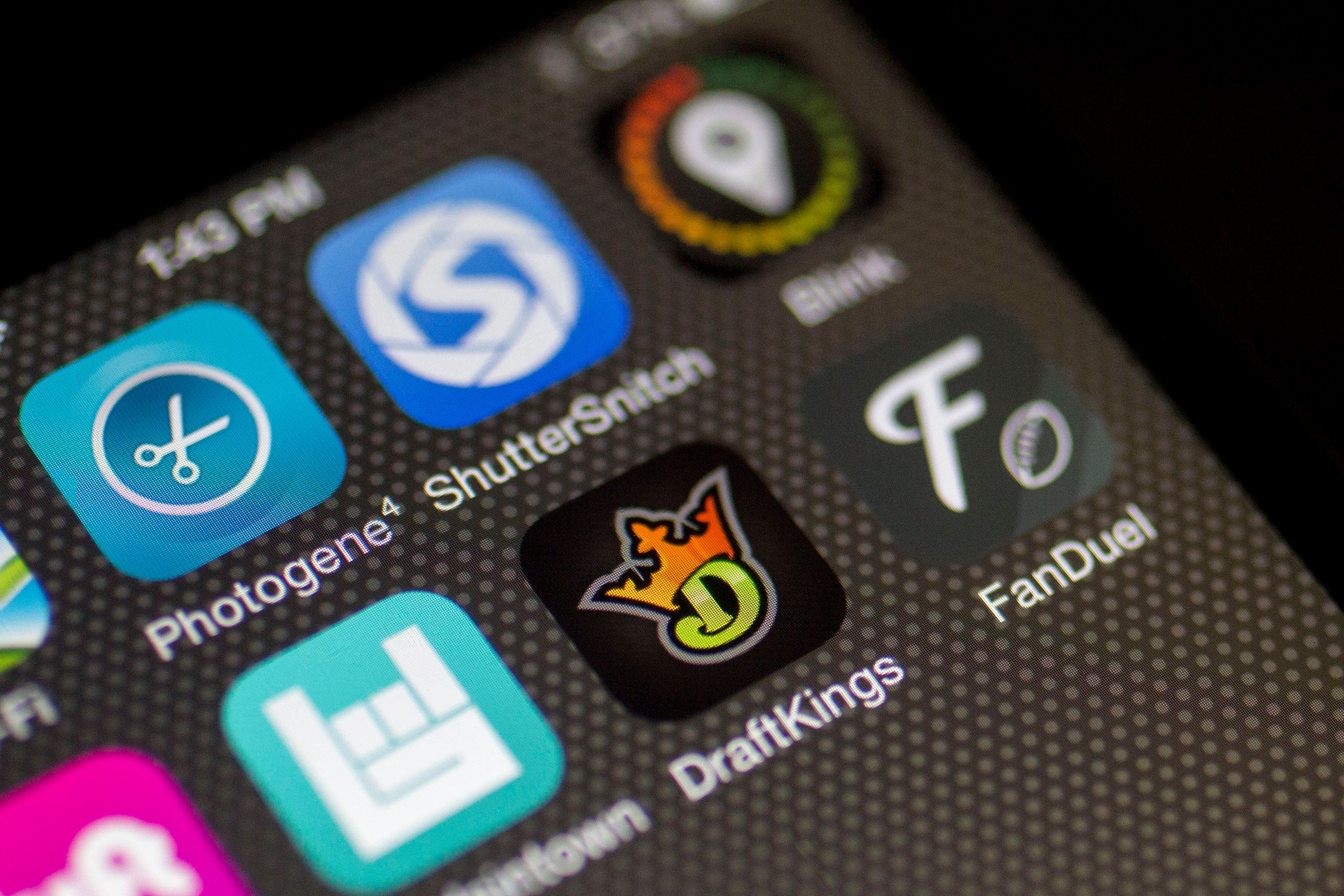 The DraftKings Inc. and FanDuel Inc. apps are displayed on an Apple Inc. iPhone in Washington, D.C., U.S., on Sunday, Oct. 4, 2015. Fantasy sports companies DraftKings Inc. and FanDuel Inc. raised a total of $575 million in July from investors including KKR & Co., 21st Century Fox Inc. and Major League Baseball to attract players to games that pay out millions of dollars in cash prizes in daily contests. Photographer: Andrew Harrer/Bloomberg via Getty Images