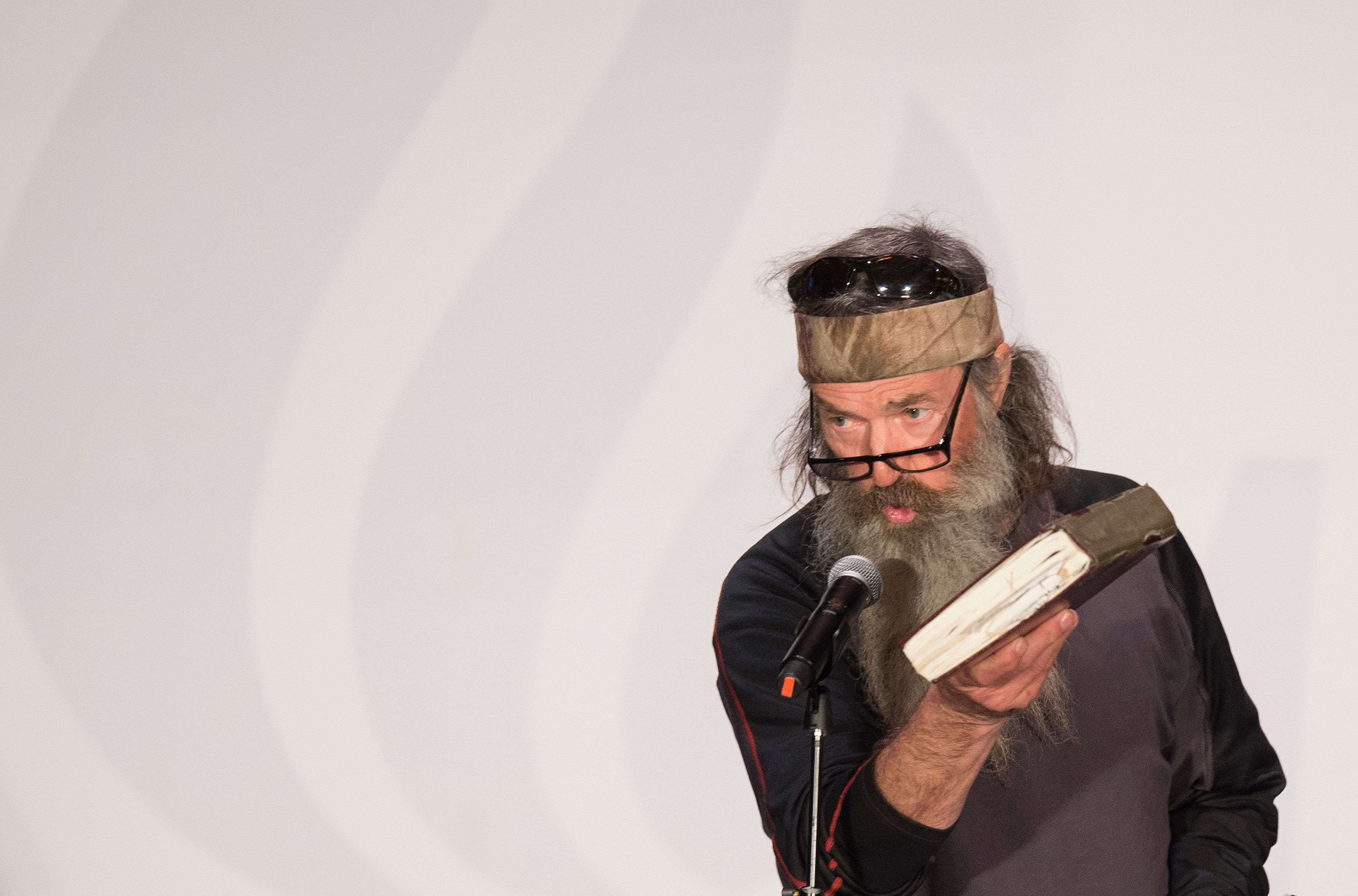 Reality TV's Duck Dynasty star Phil Robertson holds up his Bible during a campaign rally for Republican presidential candidate Ted Cruz in Charleston, South Carolina, February 19, 2016.  / AFP / JIM WATSON        (Photo credit should read JIM WATSON/AFP/Getty Images)