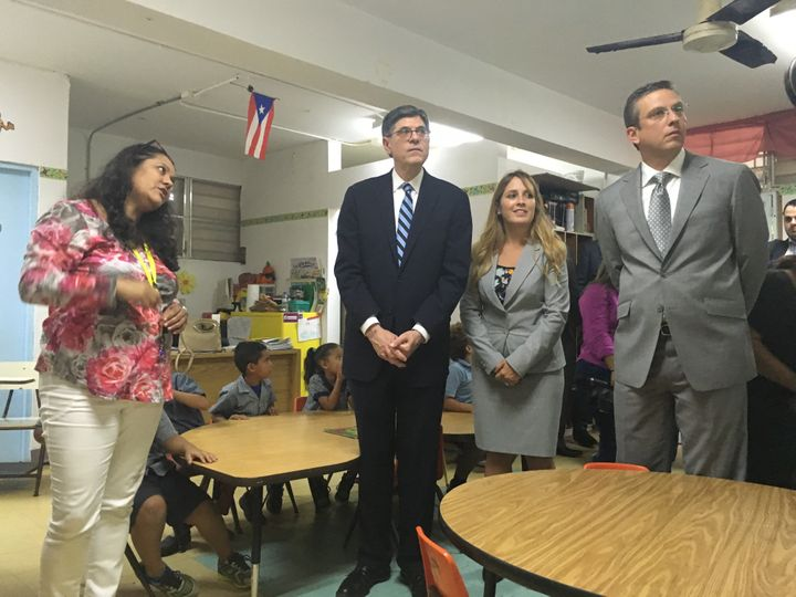 A kindergarten teacher shows Treasury Secretary Jack Lew and Puerto Rican Gov. Alejandro Garcia Padilla termite-infested wall