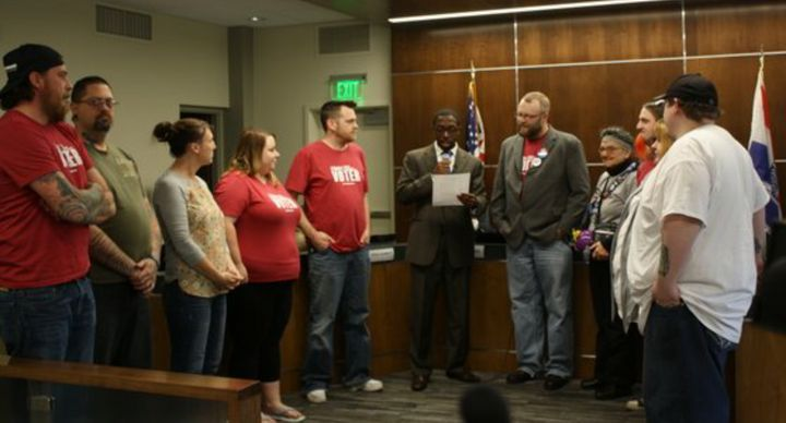 Waterloo Mayor Quentin Hart, center, reads a proclamation declaring May 5 a Day of Reason, following a secular invocation del