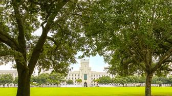 The new building of the The Citadel, seen from across the park, framed by lush trees. The Citadel, a local landmark in Charleston, is the famous Military College of South Carolina. It is one of the six Senior Military Colleges in the US. Charleston, September 2, 2015.