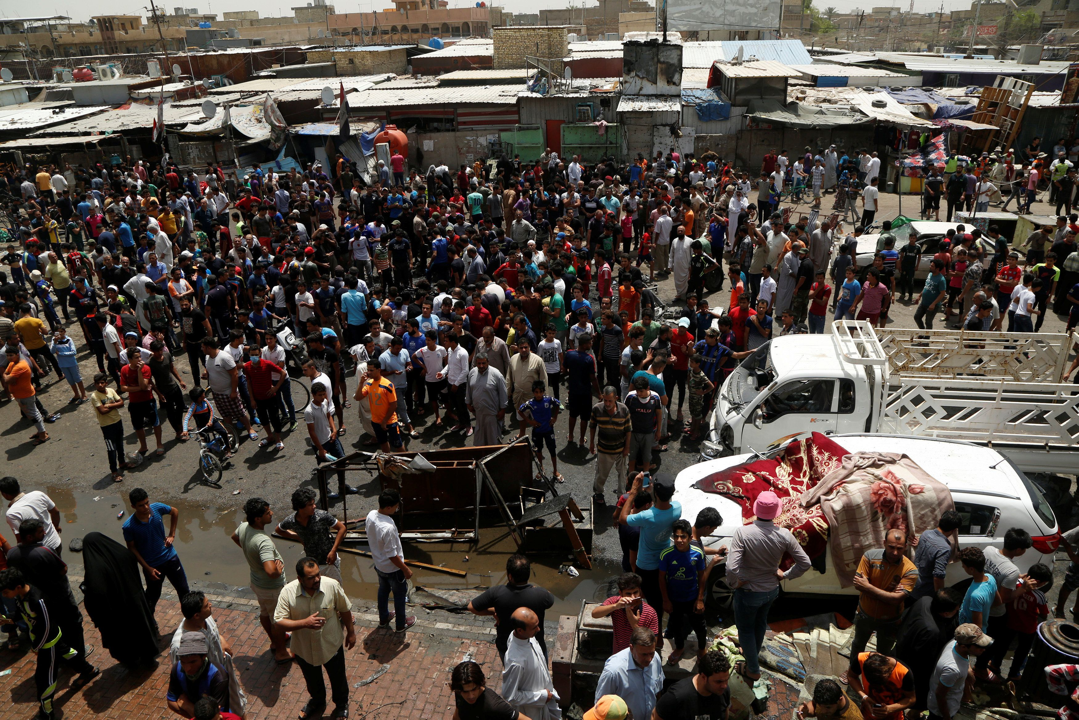 People gather at the scene of a car bomb attack in Baghdad's mainly Shi'ite district of Sadr City,