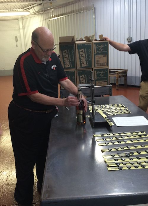 Fred Noe, Jim Beam master distiller, on Tuesday, May 10, places a label on the first bottle ofBooker's Rye, a 13-year-old uncut rye whiskey, which his father, Booker Noe, barreled in 2003.