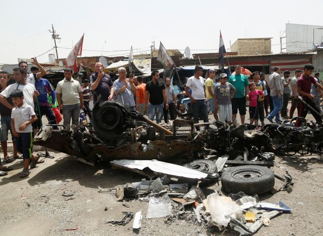 People gather at the scene of a car bomb attack in Baghdad's mainly Shi'ite district of Sadr City, Iraq,...