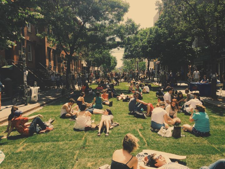 Attendees of a 2014 summer festival lounge on the grass in Williamsburg, a formerly low-income neighborhood that has seen ren