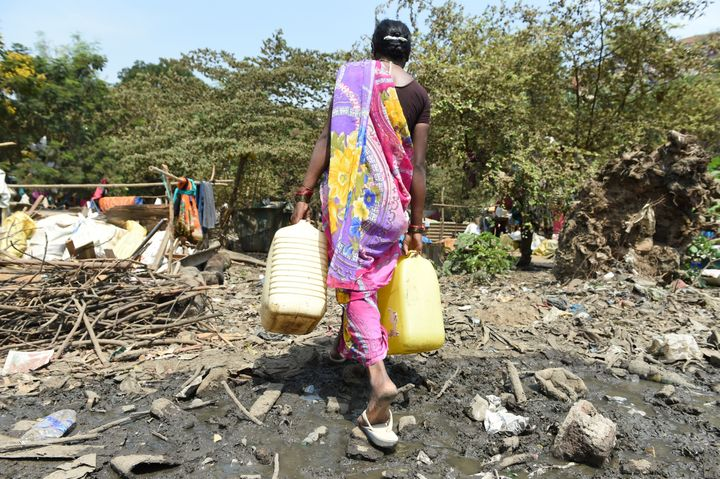 An Indian woman carries containers filled with drinking water at a makeshift camp in Mumbai. Some 300 families who have migra