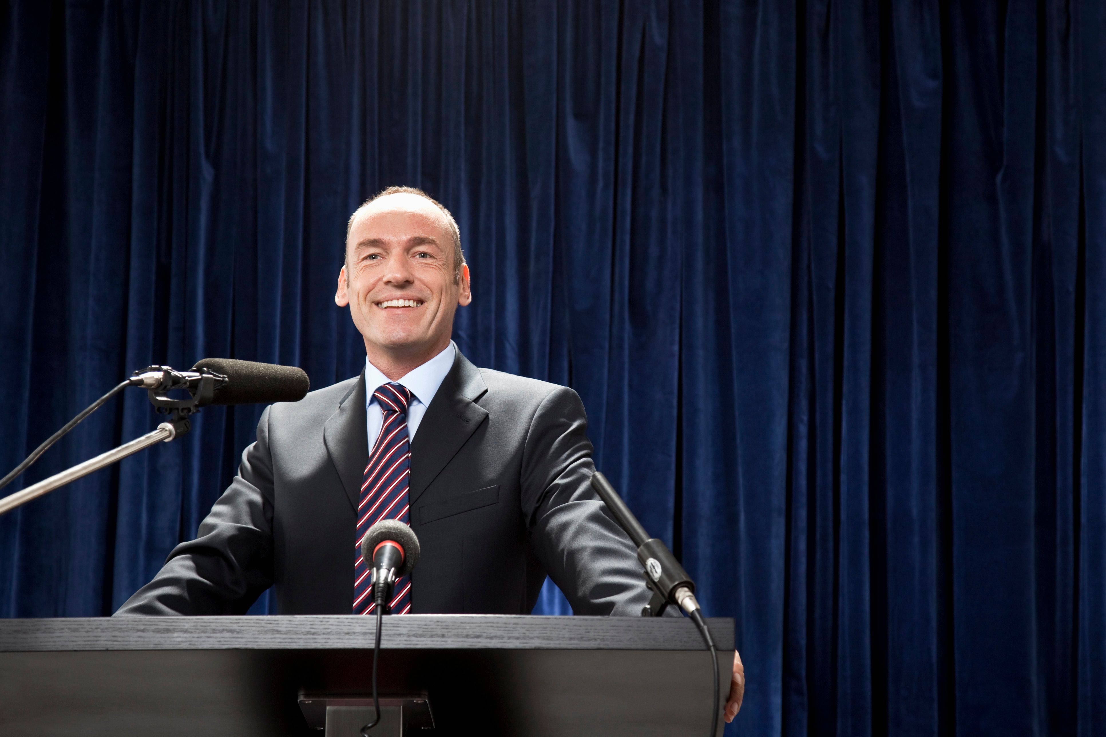 A man in a suit standing at a lectern