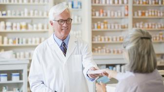 Caucasian pharmacist giving prescription to customer