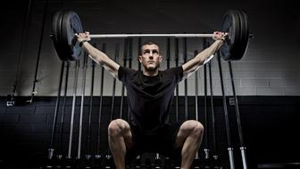 A young athletic man raises a heavy barbell above his head during a gym training workout in Hamden, Connecticut.