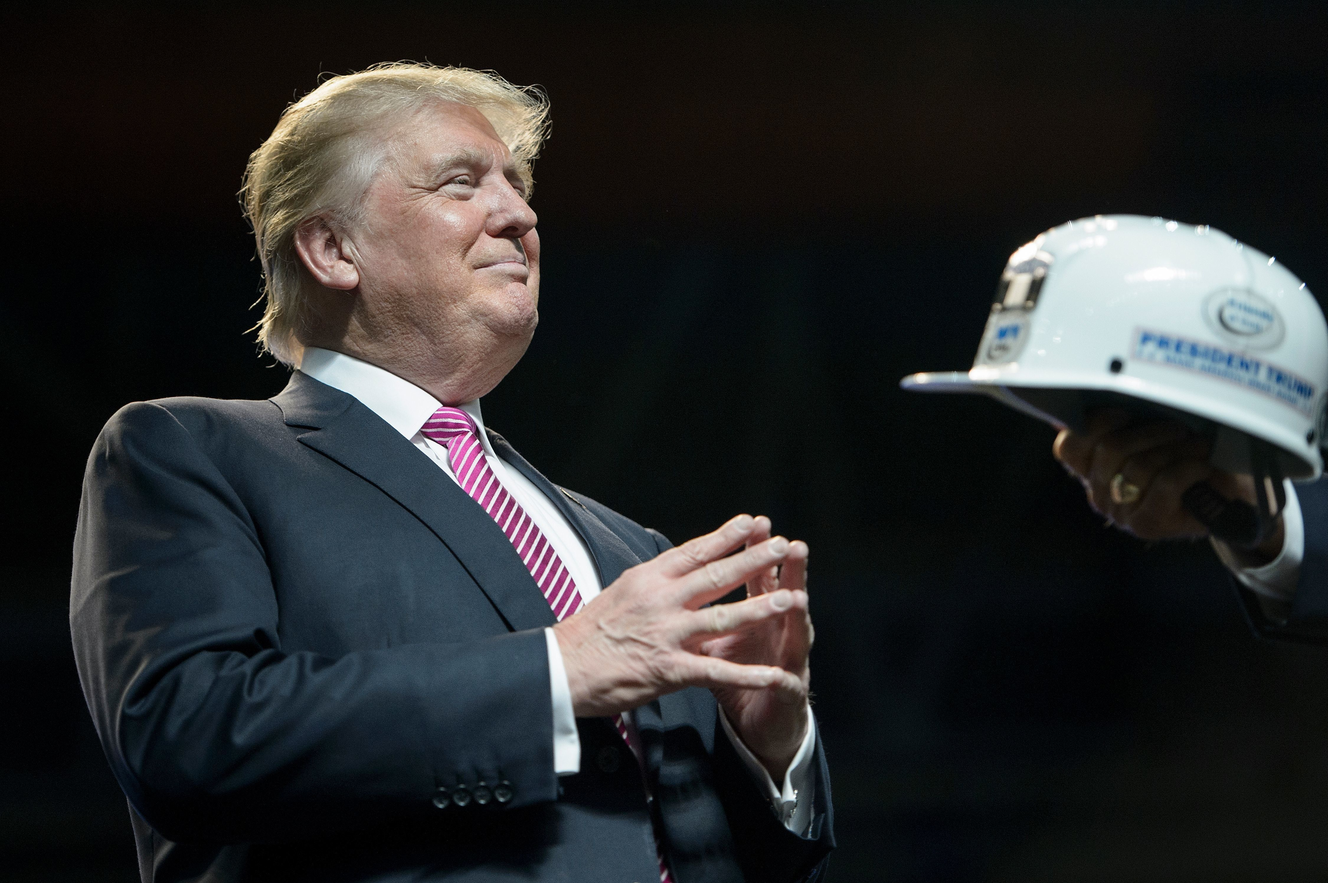US Republican presidential candidate Donald Trump is given a miner's hat during a rally May 5, 2016 in Charleston, West Virginia. / AFP / Brendan Smialowski        (Photo credit should read BRENDAN SMIALOWSKI/AFP/Getty Images)