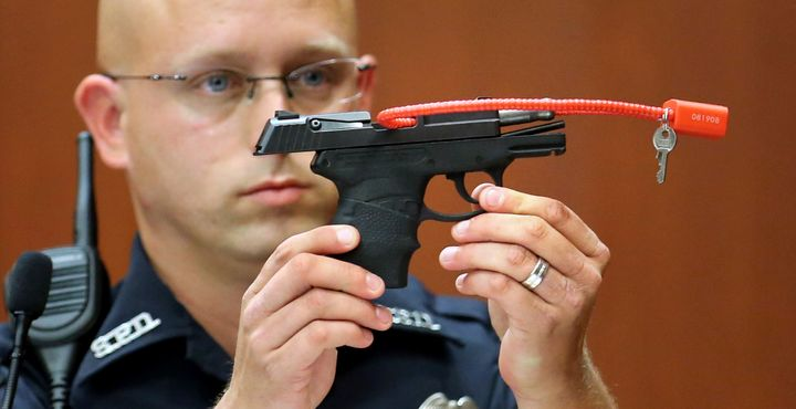 Sanford police officer Timothy Smith holds up the gun used by George Zimmerman to kill Trayvon Martin during the 2013 trial t