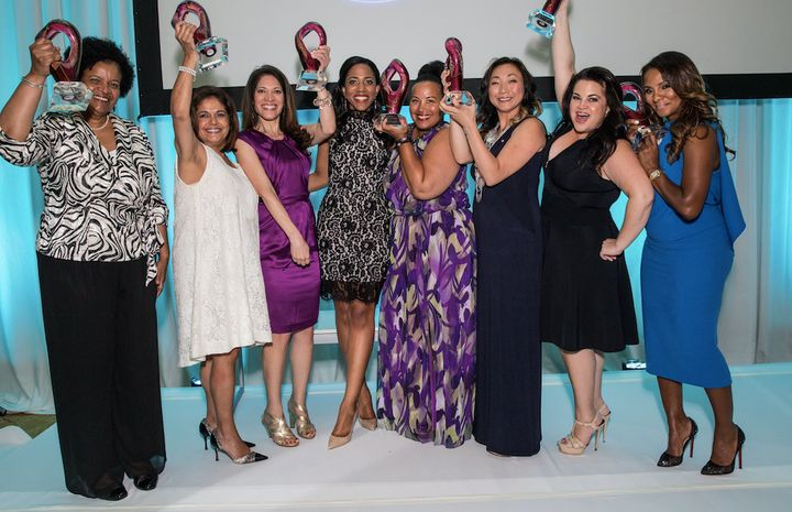 Women of color stand together in celebration of their awards at a ColorComm conference.