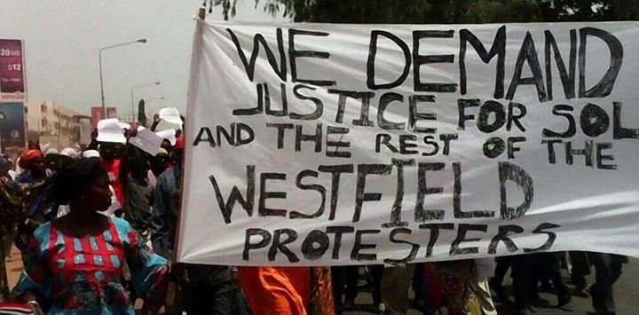 Protesters carry a sign on April 16 demanding justice for opposition members jailed by the Gambian state. Prominent figure So