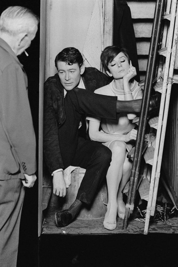Actors Peter O'Toole and Audrey Hepburn get uncomfortable together in a cramped broom cupboard in a scene from the crime cape