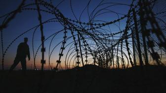 "A soldier walks past concertina wire surrounding the outside of Joint Task Force Guantanamo's Camp Delta at the U.S. Naval Base in Guantanamo Bay, Cuba March 21, 2016. Picture taken March 21, 2016. REUTERS/Lucas Jackson SEARCH ""GUANTANAMO BAY"" FOR THIS STORY. SEARCH ""THE WIDER IMAGE"" FOR ALL STORIES. ??"