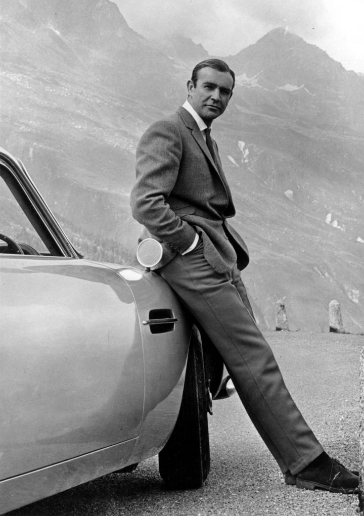 "Actor Sean Connery poses as James Bond next to his Aston Martin DB5 in a scene from the United Artists release ""Goldfinger"" in 1964."