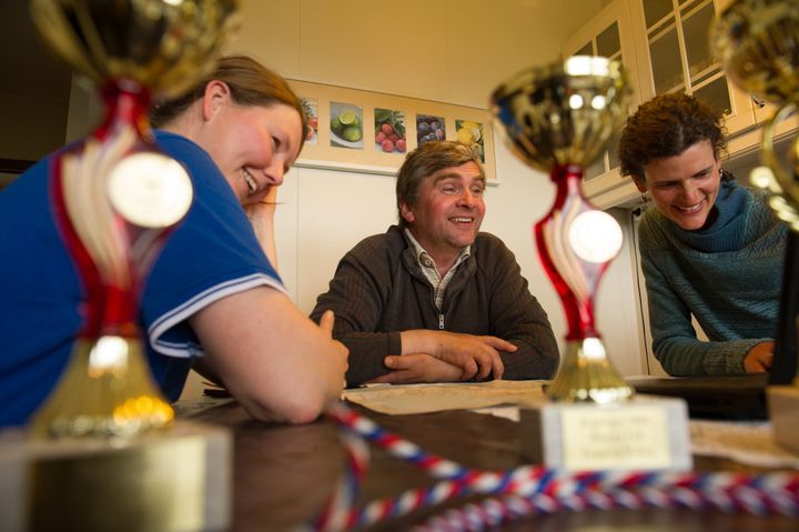 Lauga, Eyberg and Jennifer Kingsley share stories amid farming trophies spread across the kitchen table.