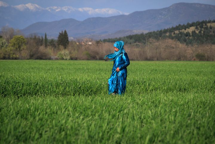 A woman walks in a field in Idomeni. Education is in high demand for Syrian refugees.