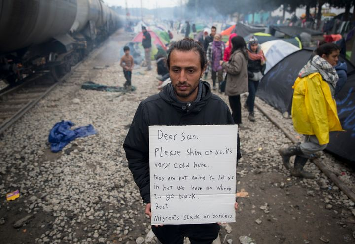 A man holds a handwritten sign near tents set up beside railway tracks at the northern Greek border point of Idomeni.