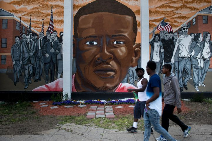 People pass a mural depicting Freddie Gray in Baltimore a year after the protests that were sparked by Gray's death in police