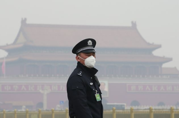 A security officer wearing a mask stands in haze in Beijing,