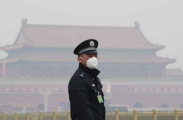 Un oficial de seguridad lleva una máscara en Beijing, China.