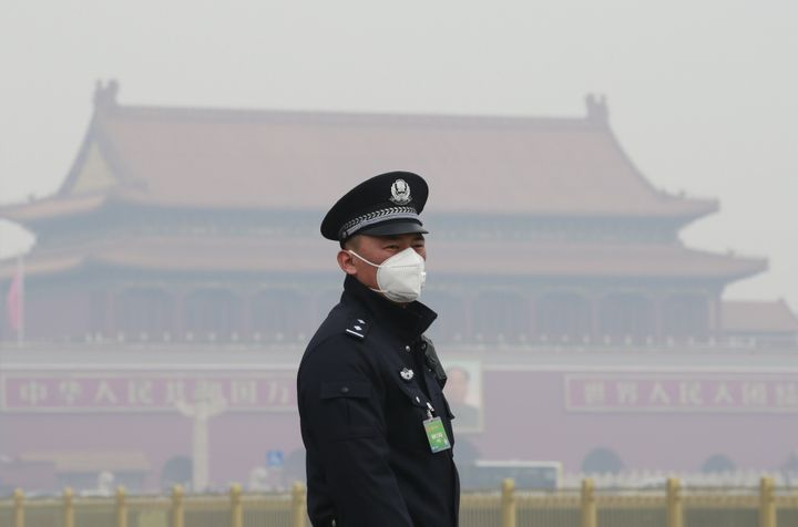 A security officer wearing a mask stands in haze in Beijing, China.
