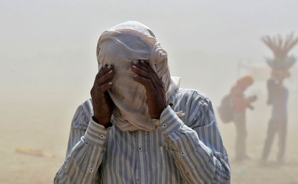 A man covers his face as he walks through a dust storm on the banks of the Ganga river in Allahabad, India.