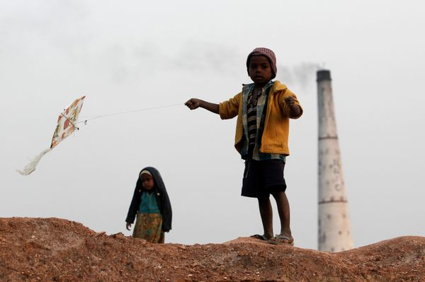 A boy flies a kite near a brick factory on the outskirts of the eastern Indian city of Patna.