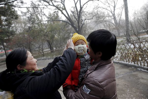 A woman fixes a protective mask on a baby during an extremely polluted day in Baoding, China.