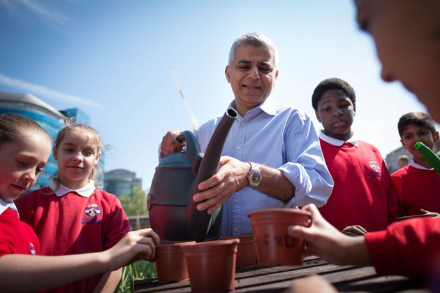 Khan helps schoolchildren plant seeds and