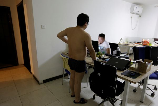 Zhang Huichao, a programmer at N-Wei (Beijing) Technology Company Limited, chats with his colleague Yan Xiaolong before he go