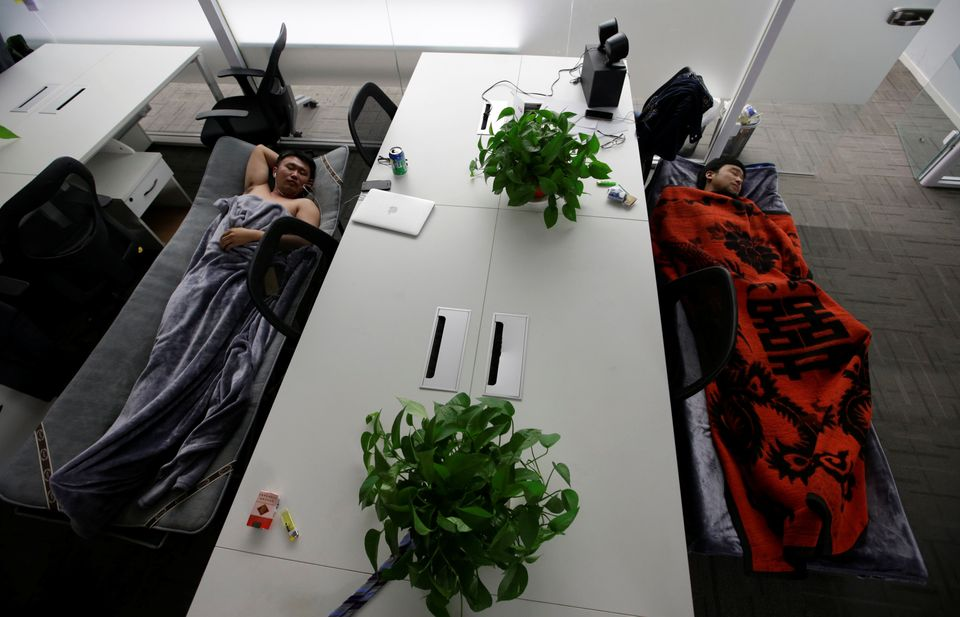 Han Liqun (L), HR manager of RenRen Credit Management Co., and IT engineer Xiang Siyang sleep on camp beds at the office afte