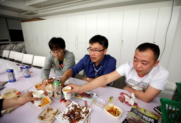 Han Liqun (C), a HR manager of RenRen Credit Management Co., drinks with his colleagues Kou Meng (L) and Ma Zhenguo after fin