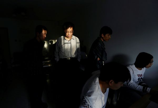 Wu Yaxiong (2nd L), CEO of N-Wei (Beijing) Technology Company Limited, stands with his programmers in an apartment which he r
