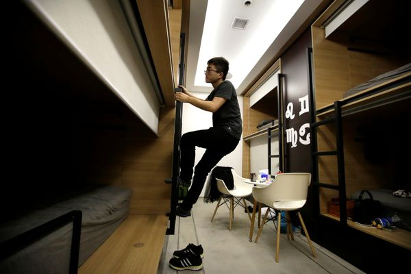 After finishing work at midnight, Du Xianchang, a R&D engineer at BaishanCloud, climbs up a ladder as he goes to bed in a