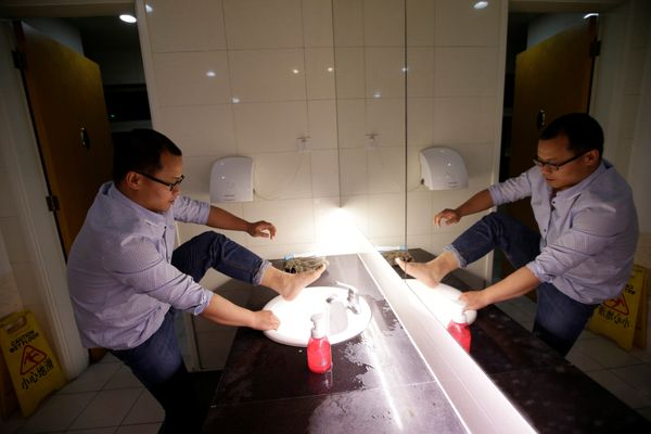 Liu Zhanyu, a client manager at DouMiYouPin, washes his feet at the office's bathroom before going to sleep after finishing w