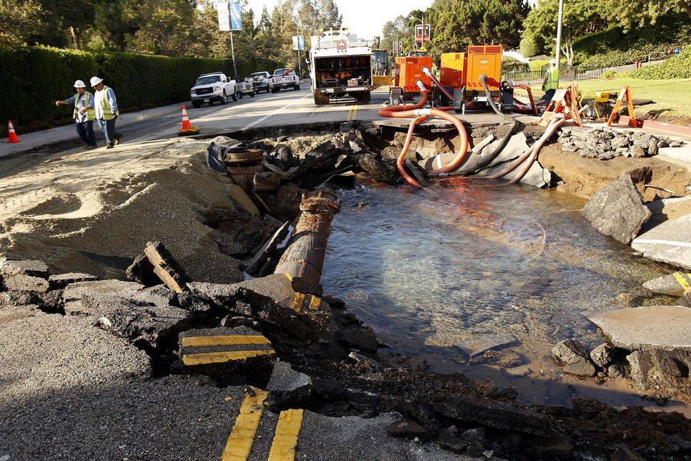 Work crews assess the damage to a ruptured 90-year-old water main in Los Angeles in 2014.