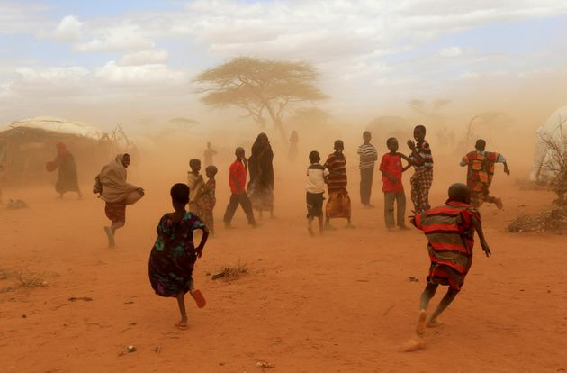 Refugees run from a cloud of dust at the Dagahaley refugee camp in