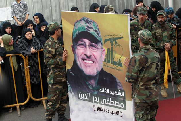 Hezbollah members carry a portrait of to commander Mustafa Badreddine during his funeral in Beirut on...