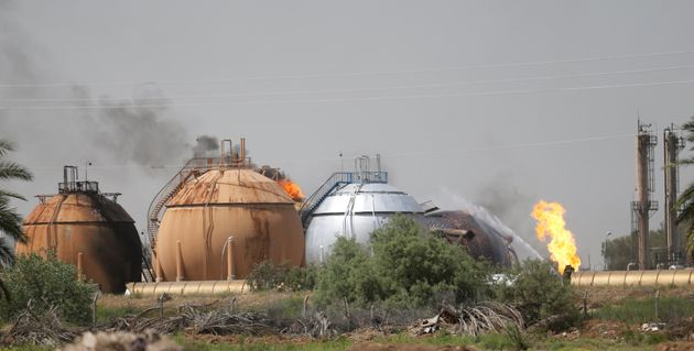 Smoke rises from gas storage tanks after a bomb attack against a state-run cooking gas factory in Taji...