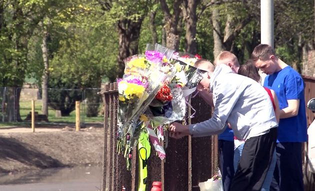 People leave floral tributes beside the Forth and Clyde