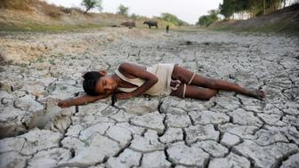 ALLAHABAD, UTTAR PRADESH, INDIA - 2016/05/14: A child lies down on a dry bed of parched mud that is the dried up River Varuna at Phoolpur. Much of India is reeling from a heat wave and severe drought conditions that have decimated crops, killed livestock and left at least 330 million Indians without enough water for their daily needs. (Photo by Prabhat Kumar Verma/Pacific Press/LightRocket via Getty Images)