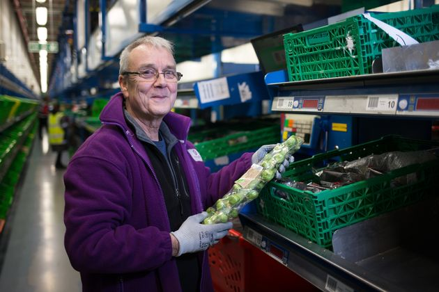 An Ocado staff member packing sprouts at