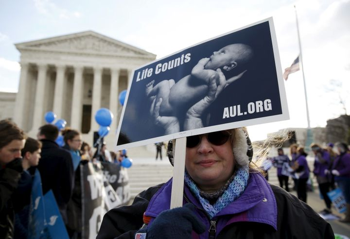 A protester holds up a sign in front of the U.S. Supreme Court on the morning the court takes up a major abortion case focusi