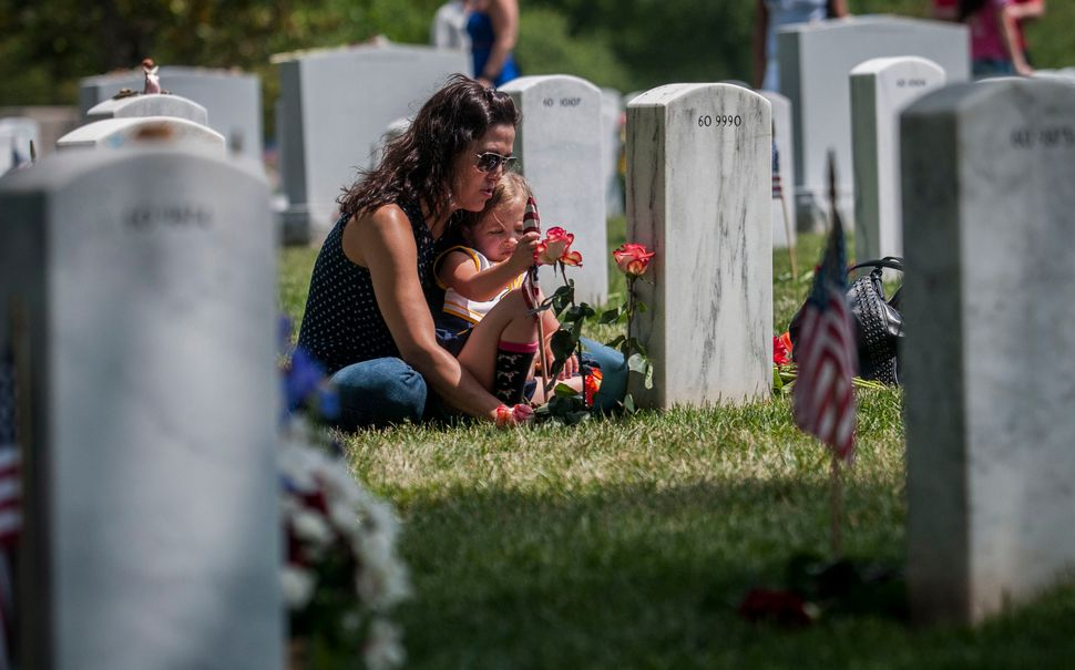 Angela Spraul and her daughter Ava, 4, sit at the grave of her husband, John Spraul, U.S. Navy, on Memorial Day at Arlington