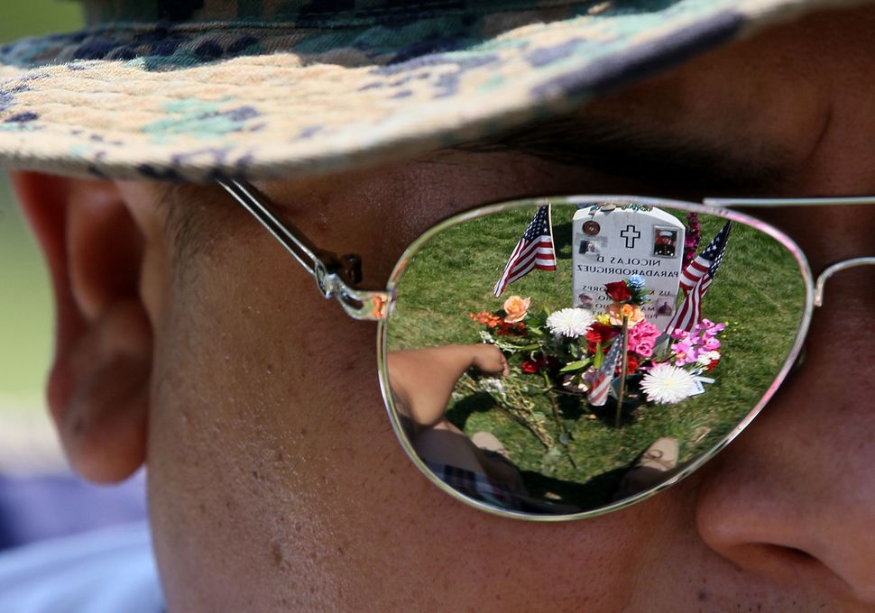 Ricky Parada sits at the grave of his little brother Cpl. Nicolas D. Parada Rodriguez, who was killed in Afghanistan, on