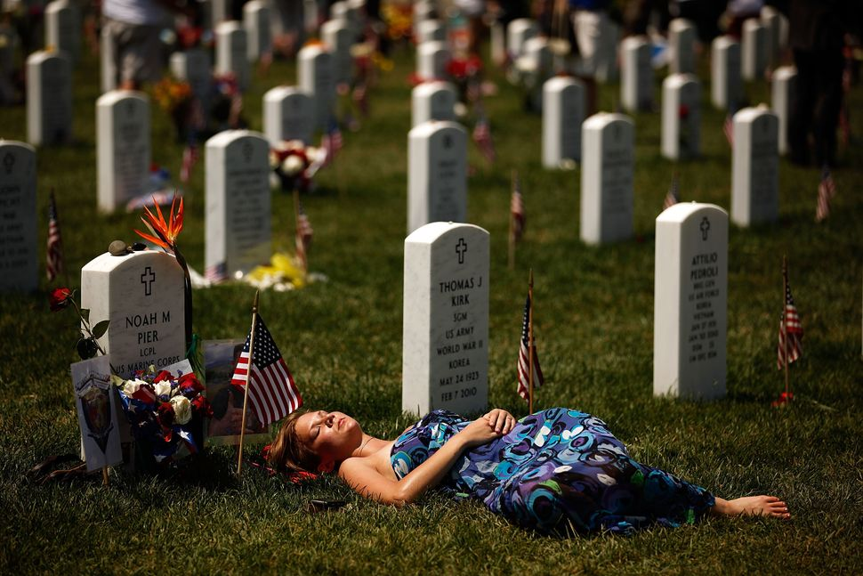 A young woman lays down on the grave of U.S. Marine Corps Lance Corporal Noah Pier on Memorial Day at Arlington National Ceme