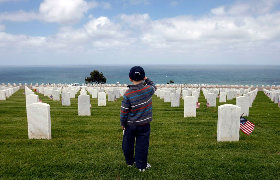 Nathaniel Marley, 4, salutes the graves of service men and women as well as his grandpa as he is taught to pay respects and s