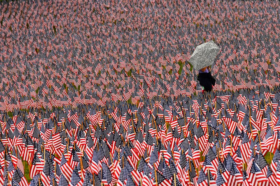 A pedestrian carrying an umbrella walks through a Memorial Day display of United States flags on the Boston Common in Boston,